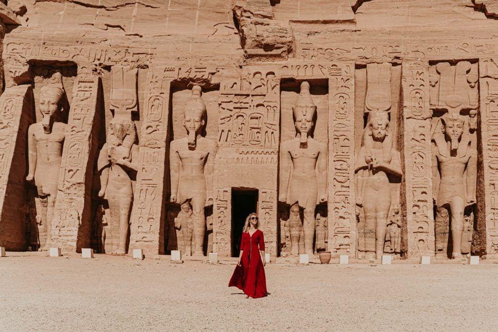girl in a red dress walks in front of the abu simbel complex with colossal statues