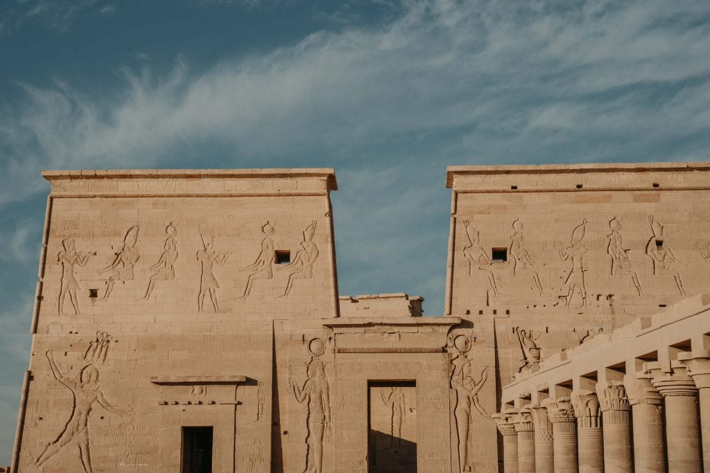 a temple facade with intricate designs - philae temple on our luxury nile cruise