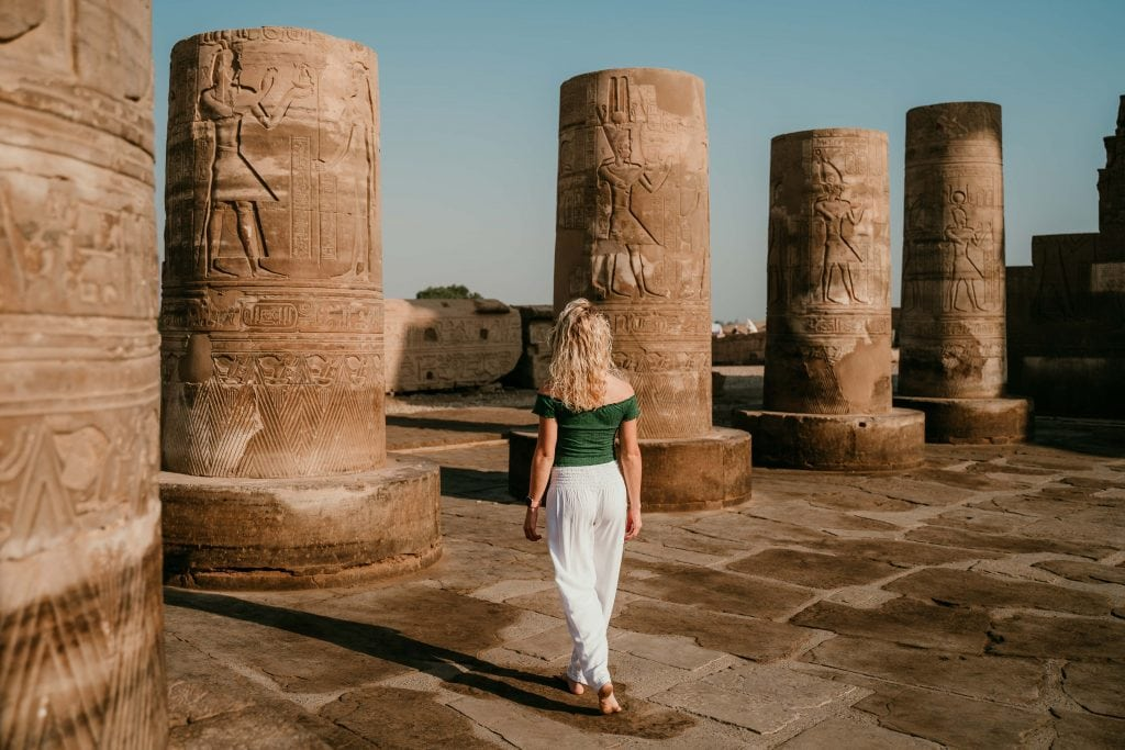 a girl in white pants and a green top walks between ancient pillars during an excursion from her aswan to luxor cruise