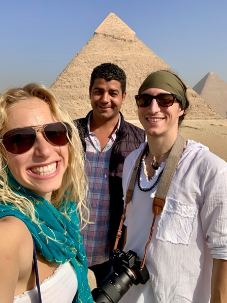 two tourists stand with their tour guide in front of the pyramids