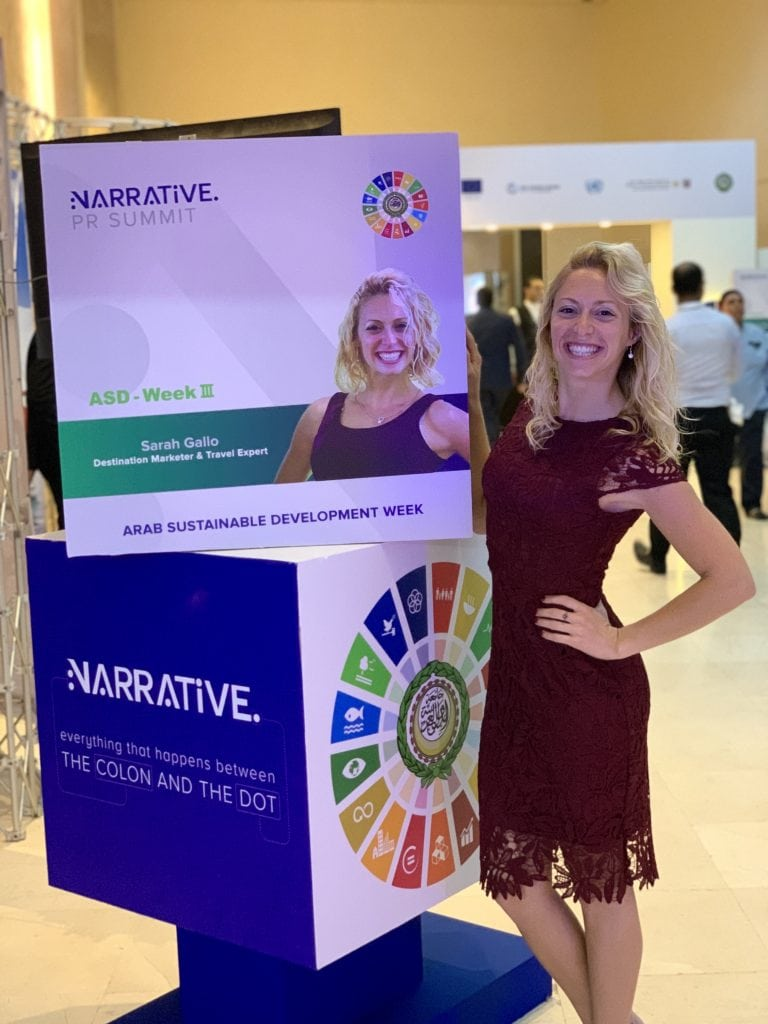 blonde girl in wine color dress stands beside an image of herself at a conference for responsible tourism