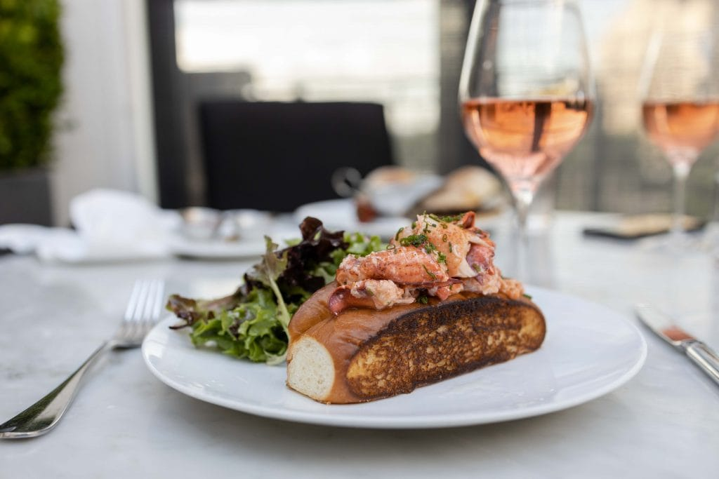 a delicious lobster roll with a glass of rose at restoration hardware