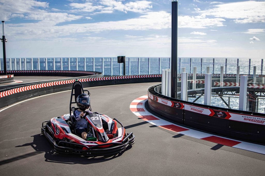 a girl goes along the speedway on the norwegian encore - the largest racetrack at sea!