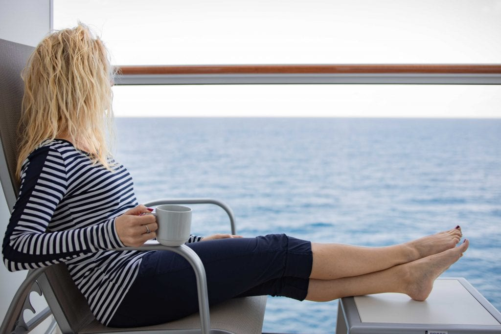 a girl wearing anatomie clothing lounges on her cruise balcony
