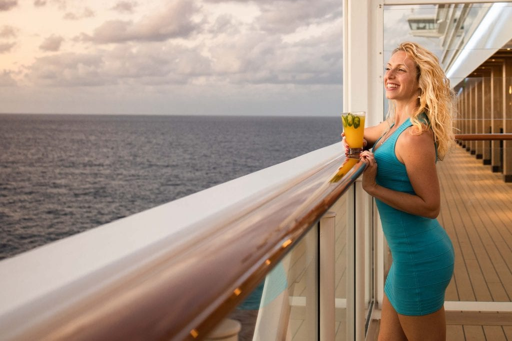 a girl overlooks the ocean - with cocktail in hand - from the deck of the norwegian encore