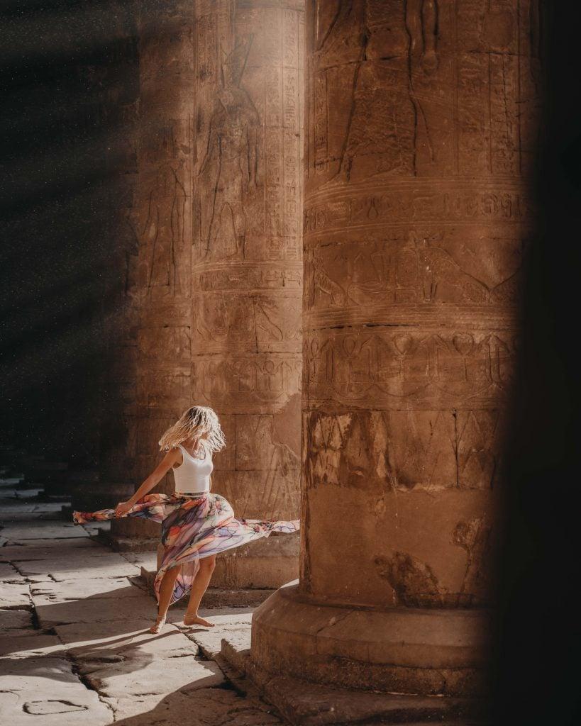 a girl spins between pillars at an ancient temple