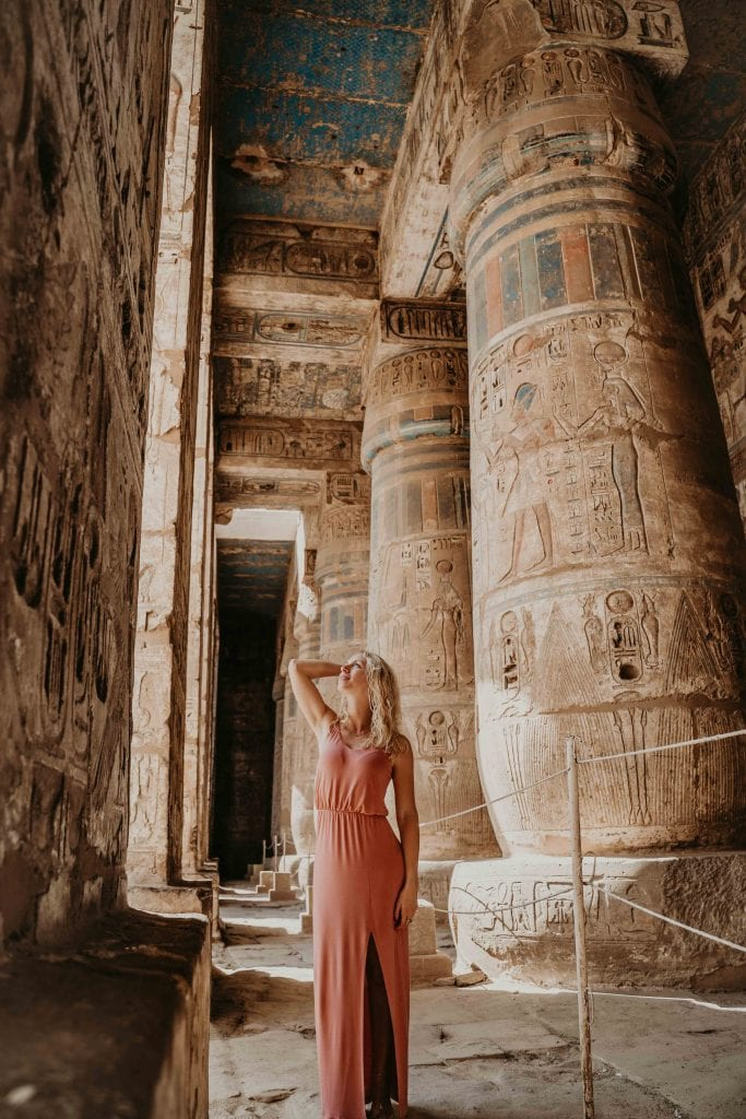 girl stands between incredibly well-preserved pillars at the medinet habu temple