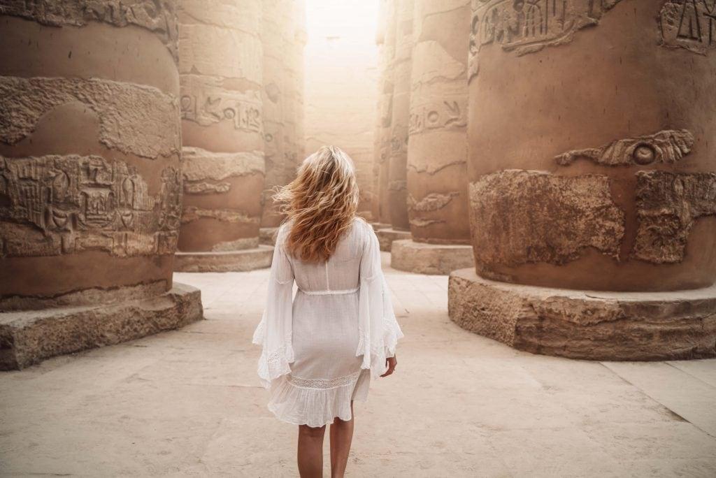 girl in white dress walks through large pillars with hieroglyphs in karnak temple on her luxury nile cruise