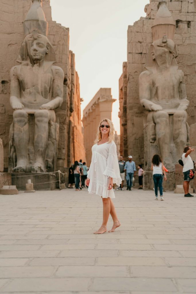 a girl stands in front of luxor temple during her luxury nile cruise