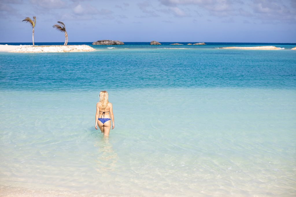 girl wades into water at great stirrup cay as a day trip off the norwegian sky