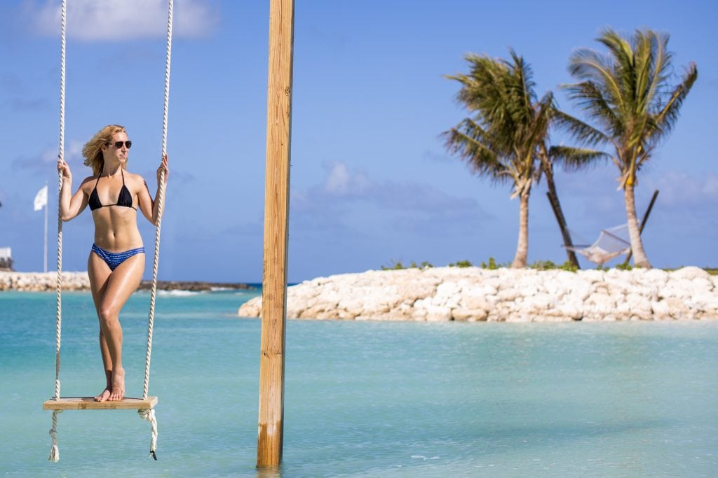girl stands on swing at great stirrup cay - norwegian sky