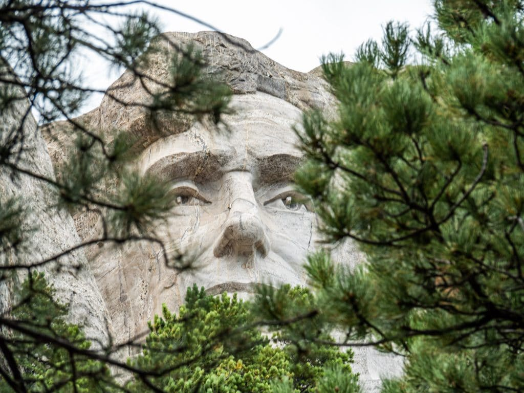 abraham lincoln on mount rushmore pictured between the trees