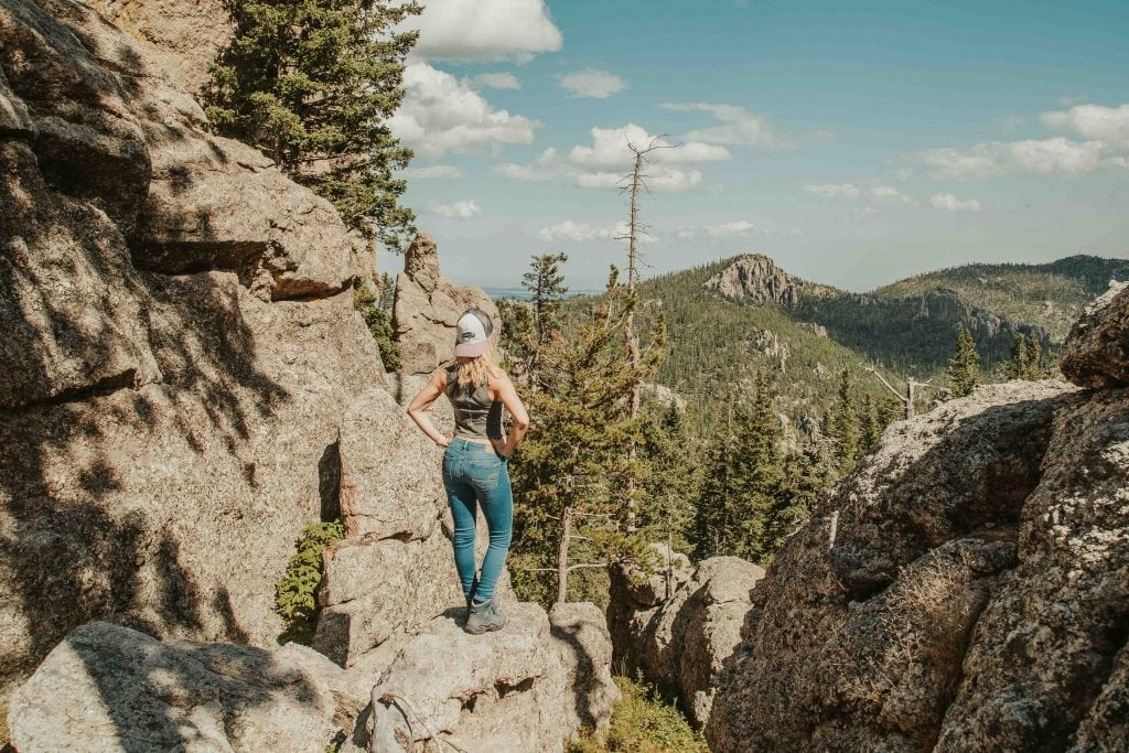 a girl stands on the ledge at the end of the cathedral spires trail in custer state park