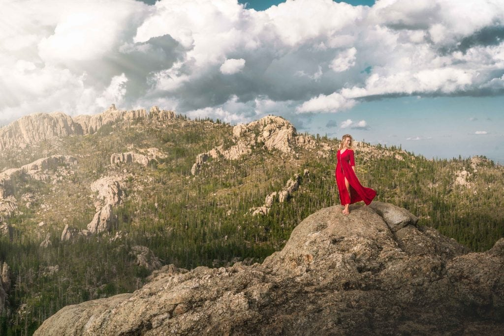 a girl stands atop little devils tower in custer state park south dakota