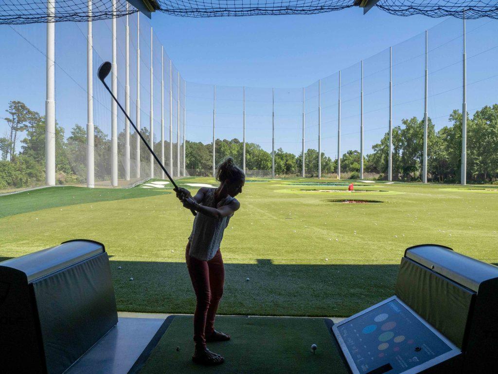 a girl swings a golf club at topgolf myrtle beach