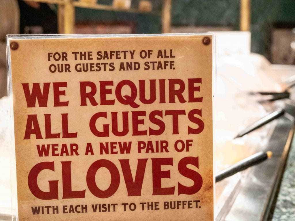 a sign that says that all guests are required to wear a new pair of gloves with each visit to the buffet in myrtle beach