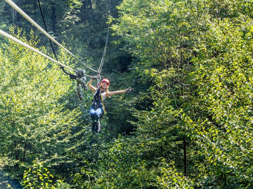 a girl in a red helmet ziplines through the forest - wvu canopy zipline tour