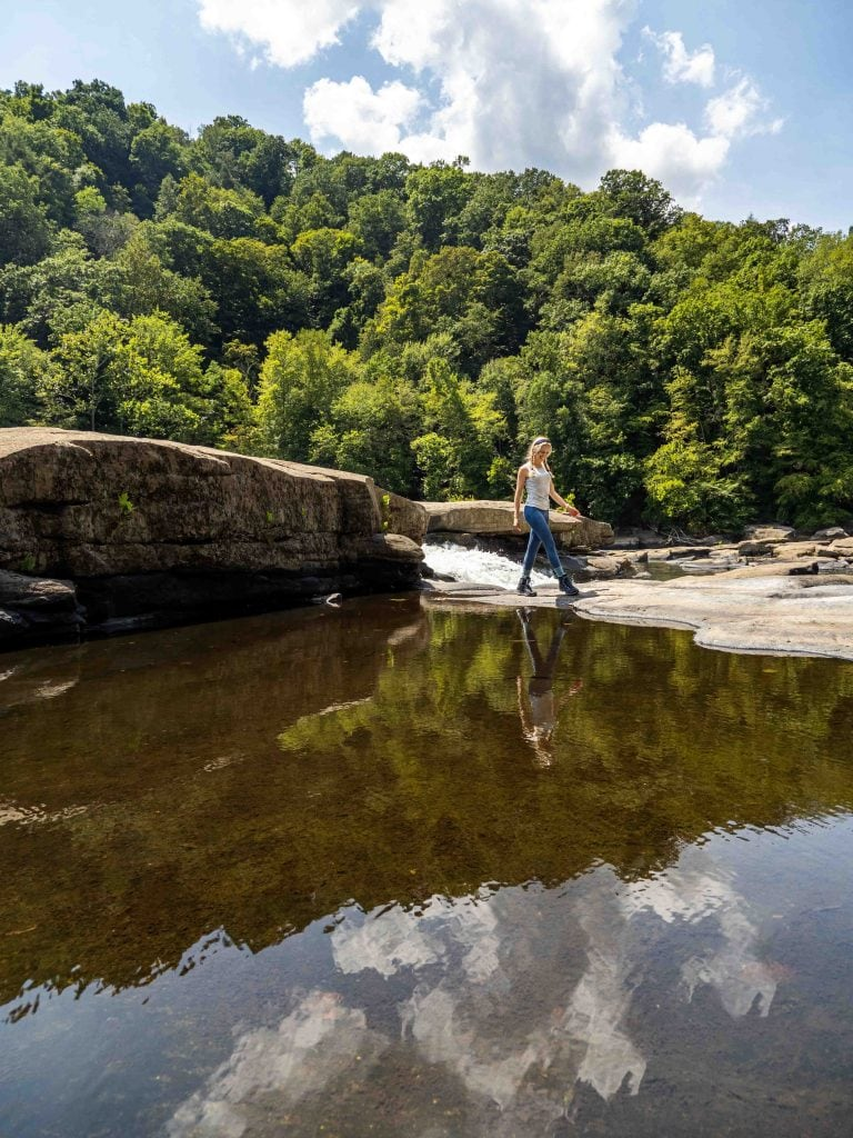 a girl walks around a lake and waterfall in morgantown, west virginia