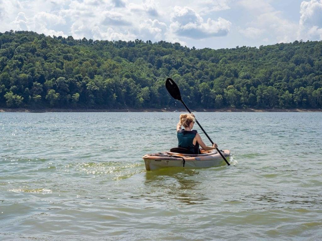 a girl kayaks on tygart lake in west virginia