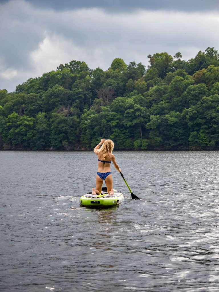 a girl on a stand up paddle board on cheat lake in morgantown west virginia