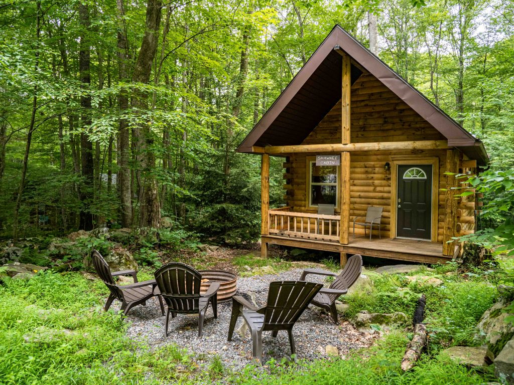 a cute log cabin sits in the woods with a fire pit out front - cabins near morgantown wv